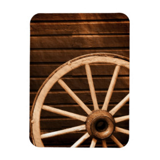 Wagon wheel leaning against old wooden wall magnet