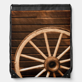 Wagon wheel leaning against old wooden wall drawstring bag