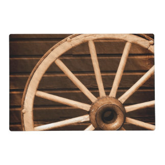 Wagon wheel leaning against old wooden wall placemat