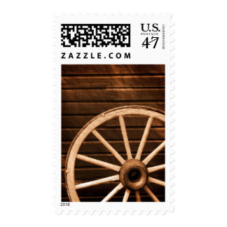 Wagon wheel leaning against old wooden wall postage