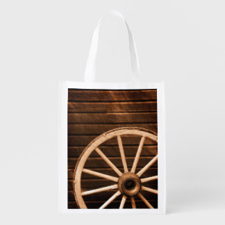 Wagon wheel leaning against old wooden wall reusable grocery bag