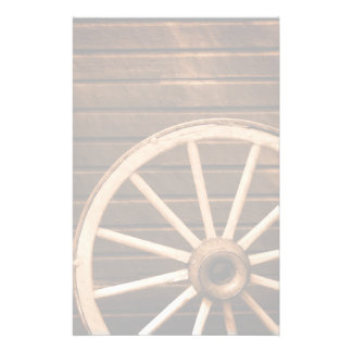 Wagon wheel leaning against old wooden wall stationery
