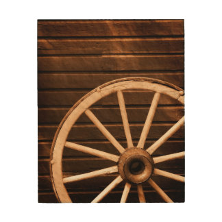 Wagon wheel leaning against old wooden wall wood canvas