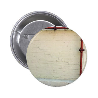 Wall of yellow plaster with cracks pinback button