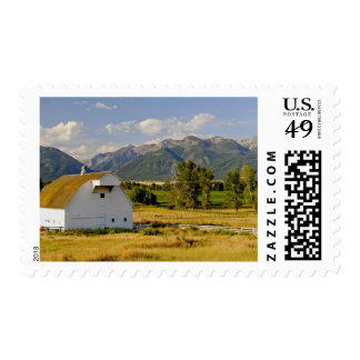 Wallowa Mountains and white barn in field Postage