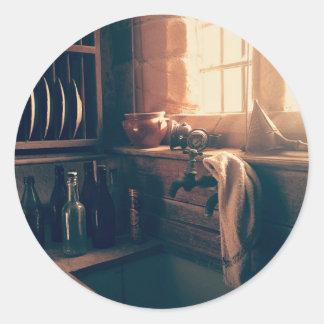 Warm light in a rustic kitchen classic round sticker