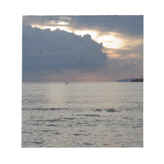 Warm sea sunset with cargo ship and a small boat notepad
