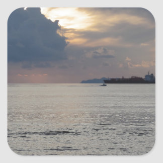 Warm sea sunset with cargo ship and a small boat square sticker