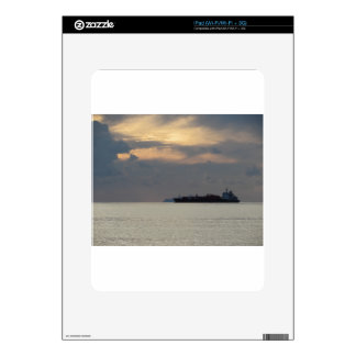 Warm sea sunset with cargo ship at the horizon skin for the iPad