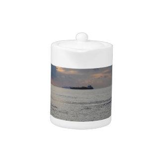 Warm sea sunset with cargo ship at the horizon teapot