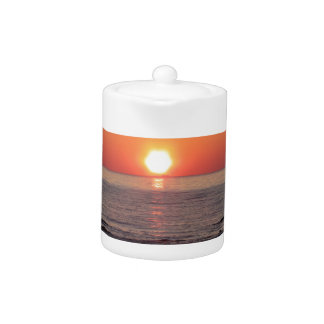 Warm sea sunset with cargo ship in the background teapot