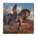 """Warrior and War Horse Tile<br><div class=""""desc"""">On endless grassy plains, an American Indian warrior sits on the back of his trusted war horse and watches as the sun sets in a sky filled with puffy clouds. The Native American man carries a tomahawk and wears red and black war paint. The mustang has a dun and white...</div>"""