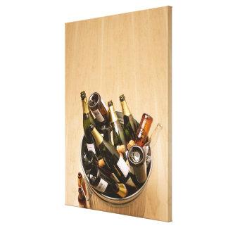 Waste bin full of empty champagne bottles on canvas print