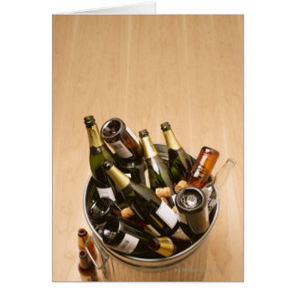 Waste bin full of empty champagne bottles on greeting card