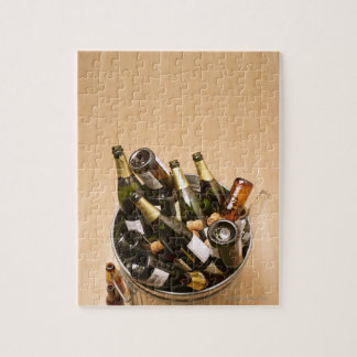 Waste bin full of empty champagne bottles on jigsaw puzzle
