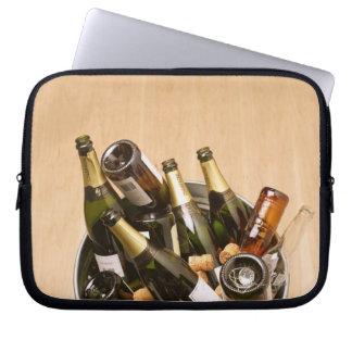 Waste bin full of empty champagne bottles on laptop sleeve