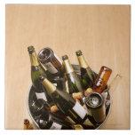 Waste bin full of empty champagne bottles on large square tile