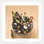 Waste bin full of empty champagne bottles on square sticker