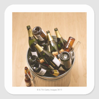 Waste bin full of empty champagne bottles on square sticker