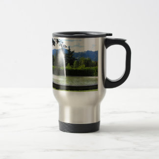 Water fountain with mountain background travel mug