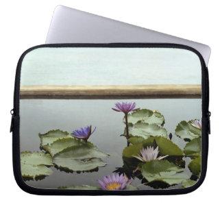 Water lilies in pond by ocean laptop sleeve