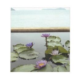 Water lilies in pond by ocean notepad