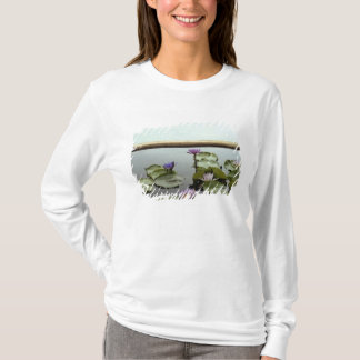 Water lilies in pond by ocean T-Shirt