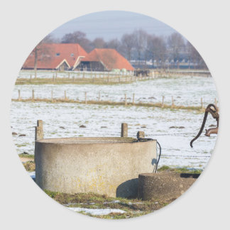 Water pump and well in winter snow landscape classic round sticker