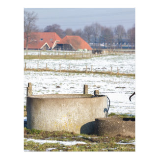 Water pump and well in winter snow landscape letterhead