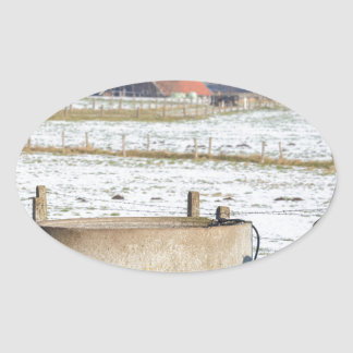Water pump and well in winter snow landscape oval sticker