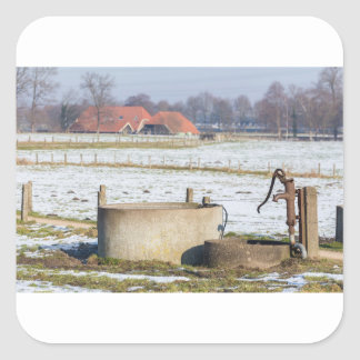 Water pump and well in winter snow landscape square sticker