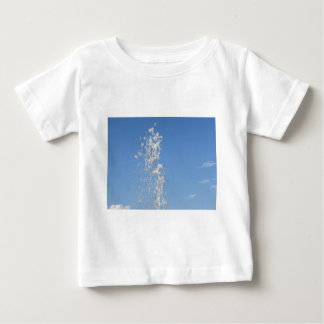 Water spraying from a fountain against the blue sk tee shirt
