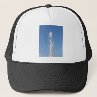 Water spraying from a fountain against the blue sk trucker hat