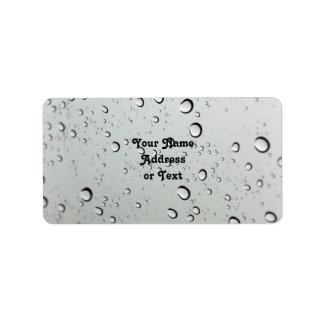 Waterdrops en el fondo de cristal etiqueta de dirección