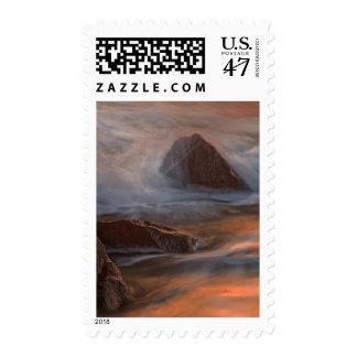 Wave crashes on shoreline rocks postage stamp