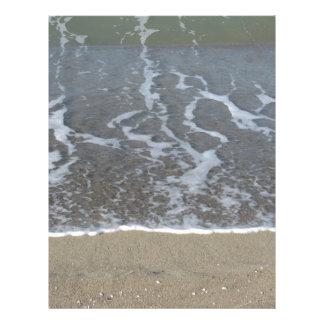 Wave of the sea on the sand beach letterhead