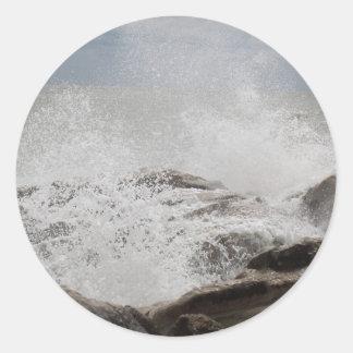Waves breaking on rocks classic round sticker