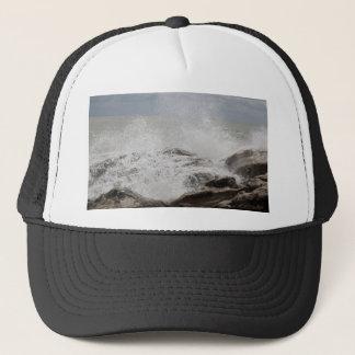 Waves breaking on rocks trucker hat