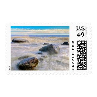 Waves crashing on shoreline rocks postage