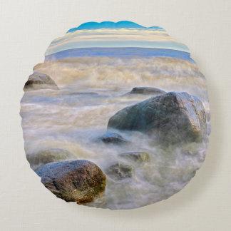 Waves crashing on shoreline rocks round pillow
