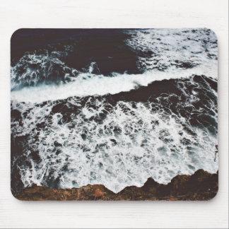 Waves create foam in dark waters mouse pad