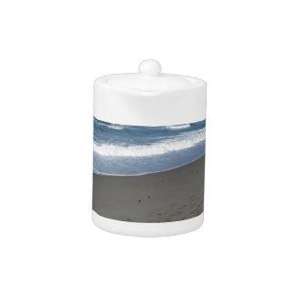 Waves of the sea on the sand beach teapot