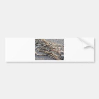Weathered fishing nets on a harbor pier bumper sticker