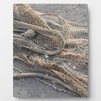 Weathered fishing nets on a harbor pier plaque