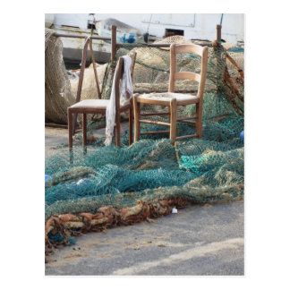 Weathered fishing nets on a harbor pier postcard