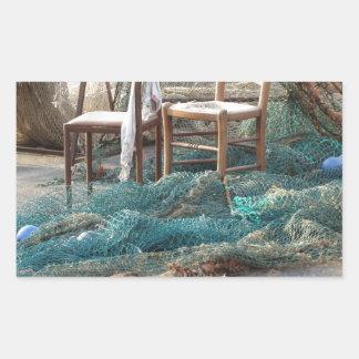 Weathered fishing nets on a harbor pier rectangular sticker