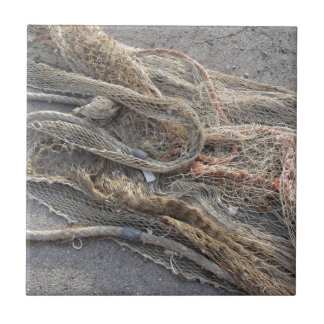 Weathered fishing nets on a harbor pier tile