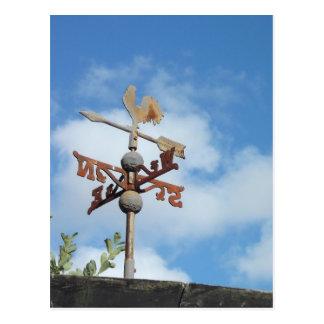 Weathervane oxidado contra el cielo azul postales