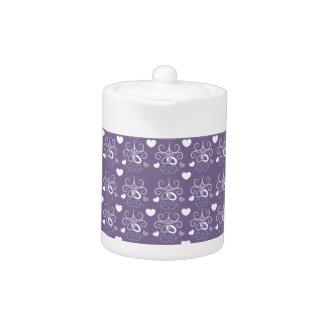 Wedding rings silver on dark purple teapot