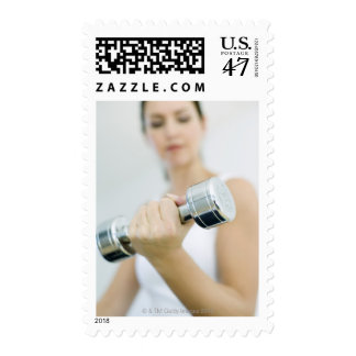 Weightlifting. Woman lifting dumbbells. This Stamp